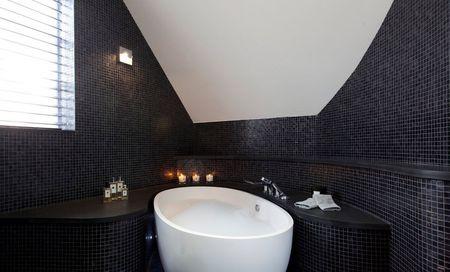 Белая ванна в сочетании с черной плиткой